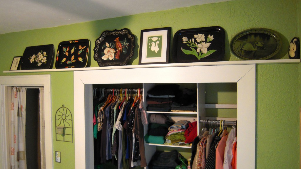 I love this! Above my closet I put up some shelves with little ledges meant for holding pictures. I've added some of my tray collection in black and greens and mixed it with one of my prints and a great little swan chalkware piece. I love this easy and cute idea for displaying them!