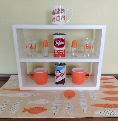 April color of the month vignette! Fave vintage: mom Florida mug, juice glasses, salt n p's, pop cans, and orange mugs. Grounded on a super awesome Vera tea towel!